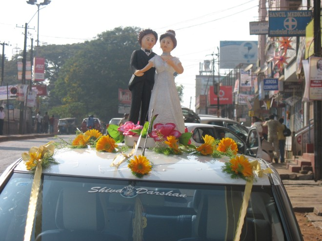 A doll couple adorned in bridal wear atop a vehicle